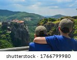 Varlaam Monastery, Meteora, Greece, Summer 2019. Two boys with their backs to each other in caps at the viewpoint of the Grand Meteora monastery watching the Varlaam monastery