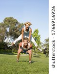 Small photo of Couple playing leapfrog in park