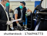 Car manager and maintenance engineer wearing face masks while working in auto repair shop during coronavirus epidemic.  - stock photo