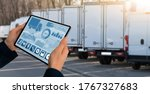 Small photo of Manager with a digital tablet on the background of trucks. Fleet management