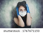 """Small photo of """"Conspiracy theory.""""Beautiful terrified young woman in a medical mask and protective surgical sterile gloves on her arm, on grunge background. Portrait of woman facing strong fear, being terrified."""