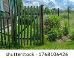A Wooden Gate Made Of A Green...