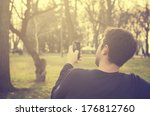 Young man sitting in the park and texting a message  - stock photo