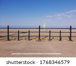 The Bray Seafront with horizon and the Irish Sea visible across the barrier. Seascape. Sunny day. Geometry and visual symmetry.