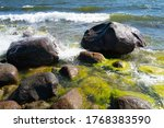 Waves hitting against the rocks. Baltic sea on sunny summer day. Little moss on the stones. Nice foam and bubbles everywhere. Amazing high resolution quick shutterspeed shots. Blue cloudless sky. Warm