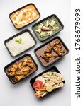 Small photo of Online Food delivery concept Indian paneer butter masala and palak paneer, mutton & chicken curry with roti and rice in plastic containers, food like butter chicken, chicken