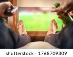 Man Sitting On A Sofa Watching...