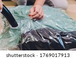 Small photo of Space saver saving seal bag sucking air out , vacuum clothing storage compressed package.