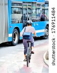Bicyclist (male or female) properly equipped with helemt in traffic, bus in background - stock photo