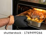 Small photo of a man in a refractory glove takes out baked food from the oven