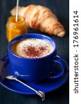 Fresh croissant with sweet jam and cup of latte coffee for breakfast. - stock photo