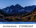 Maroon Bells in October 2019 lake peak view blue hour in Aspen, Colorado at dark night with rocky mountains and fall autumn foliage with moon in sky
