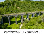Aerial drone view of a Victorian era viaduct in a beautiful green valley (Pontsarn Viaduct, Brecon Beacons, Wales) - stock photo