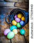 Easter eggs in the basket on rustic wooden background