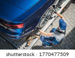 Caucasian Towing Truck Driver in His 40s Preparing Vehicle For Car Dealership Customer. Brand New Car Home Delivery on Towing Truck. - stock photo