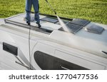 Caucasian RV Industry Worker Cleaning Camper Van Roof and Motorhome Solar Panels. Pressure Washing Recreational Vehicle Roof Equipment. - stock photo