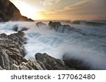 Waves Crash Over Rocks As The...