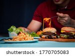 Small photo of Man holding hamburger on the wooden plate after delivery man delivers foods at home. Concept of binge eating disorder (BED) and Relaxing with Eating junk food.