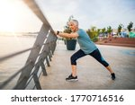 Small photo of A senior woman stretches during her workout. Mature woman exercising. Portrait of fit elderly woman doing stretching exercise in park. Senior sportswoman making stretch exercises