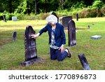 Elderly Woman Kneels Besides...