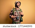 Young hiker man with curly hair and beard hiking wearing backpack and water canteen angry and mad screaming frustrated and furious, shouting with anger. Rage and aggressive concept. - stock photo