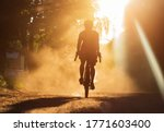A Man Riding A Bicycle On A...