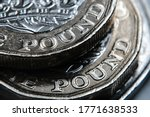 """British one Pound coins on top of each other with word """"Pound"""" in a main focus. Macro. Selective focus. Concept."""