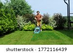 Lawn mowing in a beautiful landscape. An adult man using a lawn mower with a grass catcher mows overgrown grass on the lawn. - stock photo