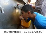 Small photo of Palestinians fill water from pipes provided by the United Nations Relief and Works Agency (UNRWA) headquarters in the Rafah refugee camp in the Southern Gaza Strip, on July 8, 2020.