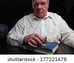 Small photo of Middle age man staring straight ahead, clutching shot glass set upon Big Book of Alcoholics Anonymous with black background