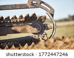 Close up of a Trencher chain in motion preparing to dig a trench in dirt