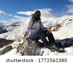 Small photo of Ljuboten, Macedonia- January 2,2018: Hiker girl with black phantom mask and hiking gaiters sitting on a rock, snow covered mountain.