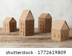 Small photo of Cardboard toy houses on wooden background. Sale or rental of housing. Neighbors in house. Comfortable life in suburbs.