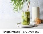 Iced Green matcha tea mixed with ice cube and milk in latte glass on white. Space for text. Close up.