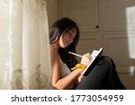 Young Hispanic Woman Writing In ...