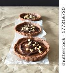 Small photo of Three chocolate tarts with cream and hazelnut on baking paper abreast