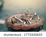Small photo of Ashtray full of cigarette butts. Used cigarette in ashtray. Dirty cigarette filter waste in clay ashtray. Toxic waste. Quit smoke or smoking cessation and lung cancer trigger concept. Tobacco product.