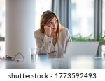 Small photo of Shot of a young businesswoman looking bored while working at her desk in a modern office. Bored secretary feeling lack of motivation or ideas tired of boring job and dull paperwork,absent-minded lazy