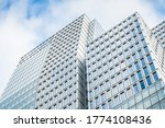 Silver office buildigns facade with blue sky n the background and reflecting in windows