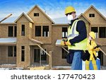 Building Construction Site with Two Contractor. One Contractor Site Manager with Tablet and Second Contractor with Small Hammer. - stock photo