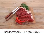 fresh raw beef meat steak's on wooden cut board over wooden table with dill and stainless steel knife - stock photo