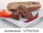 ripe beef meat hamburger on white plate with rye bun on white plate with cutlery on tablecloth - stock photo