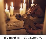 Small photo of A girl pierces a voodoo doll with needles, close-up. Esoteric and occult rituals on a wooden table in a dark room with many candles. The concept of revenge, causing harm to a rival. Magic background.
