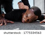 Small photo of selective focus of detained african american man lying on ground near police officer with baton, racism concept