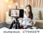 Small photo of Asian businesswoman working from home live video interaction with customers using camera device vlogging selling make up products, viral internet social media influencer interacting to live audience