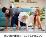 Small photo of cheerful family having fun, playing twister game at home