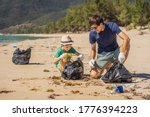 Small photo of Dad and son in gloves cleaning up the beach pick up plastic bags that pollute sea. Natural education of children. Problem of spilled rubbish trash garbage on the beach sand caused by man-made