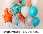 Small photo of Composition of blue, silver, orange and transparent balloons with helium. Foil balloon in the shape of a star. The concept of decorating a room with helium balloons for holidays or birthdays