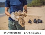 Small photo of Man in gloves pick up plastic bags that pollute sea. Problem of spilled rubbish trash garbage on the beach sand caused by man-made pollution and environmental, campaign to clean volunteer in concept