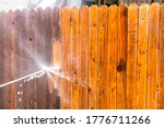Small photo of Stay at Home house repairs , Pressure Washing Fence with a high pressure washer , cleaning old dirty planks of wood on Wooden Fence in Suburb Neighborhood